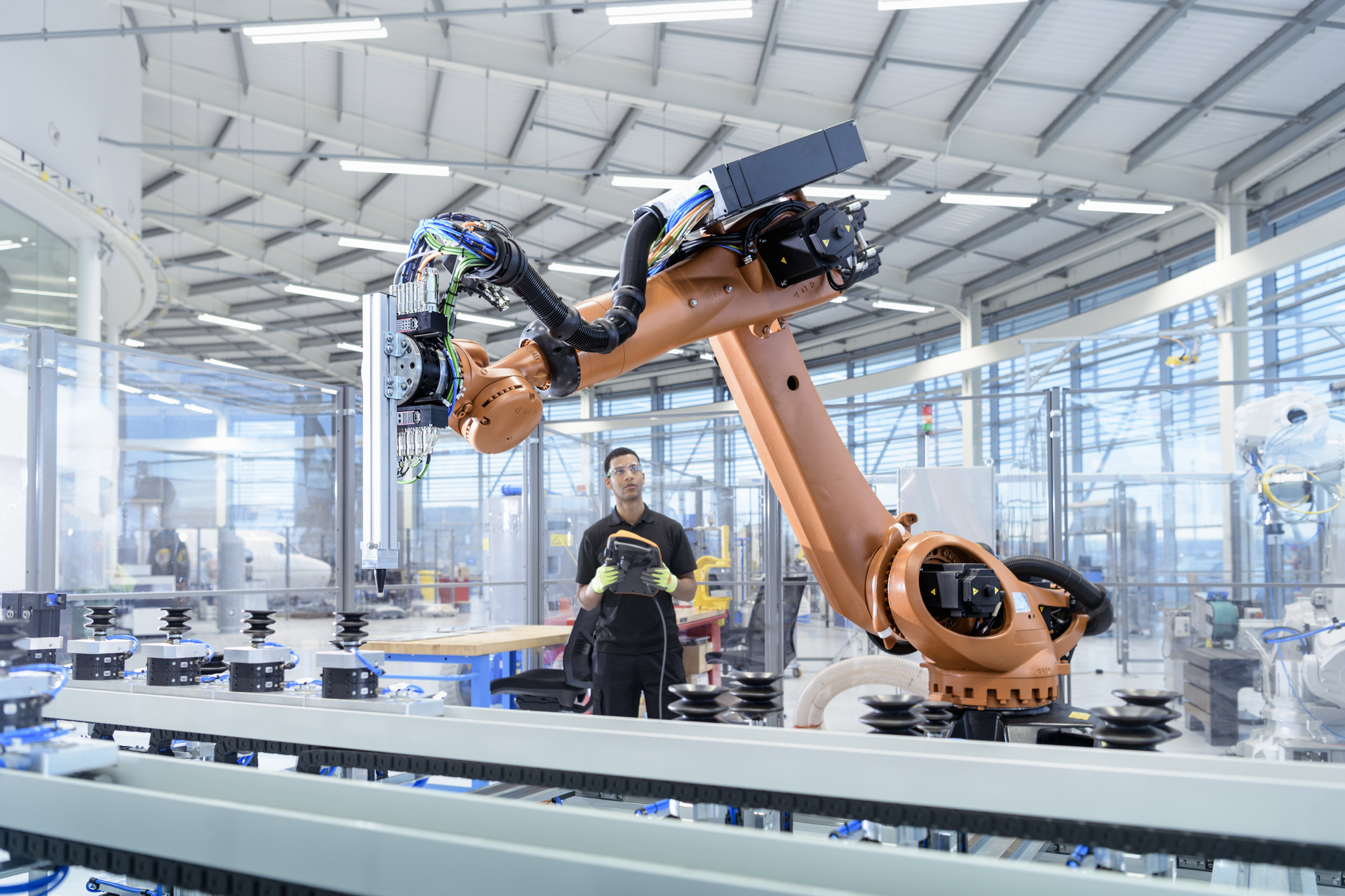 Engineer working with robotic arm on production line