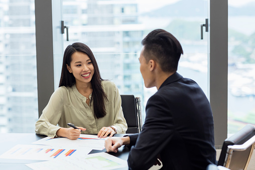 Young Asian man and woman in business meeting