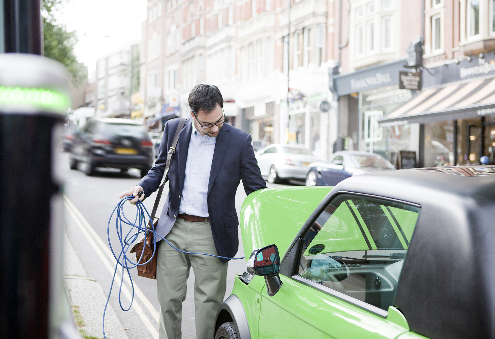 Man charging electric vehicle