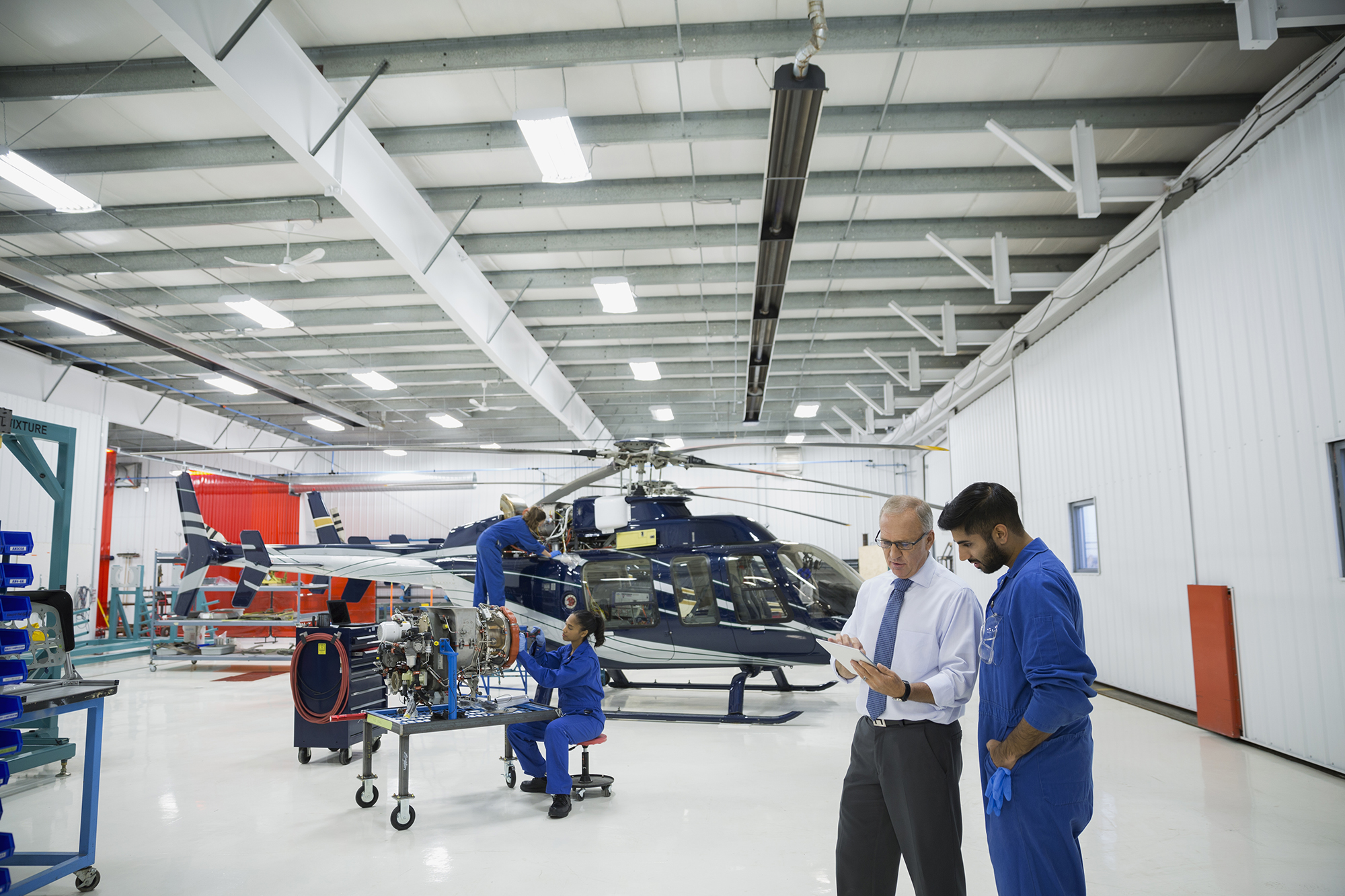 Manager and helicopter mechanic using digital tablet
