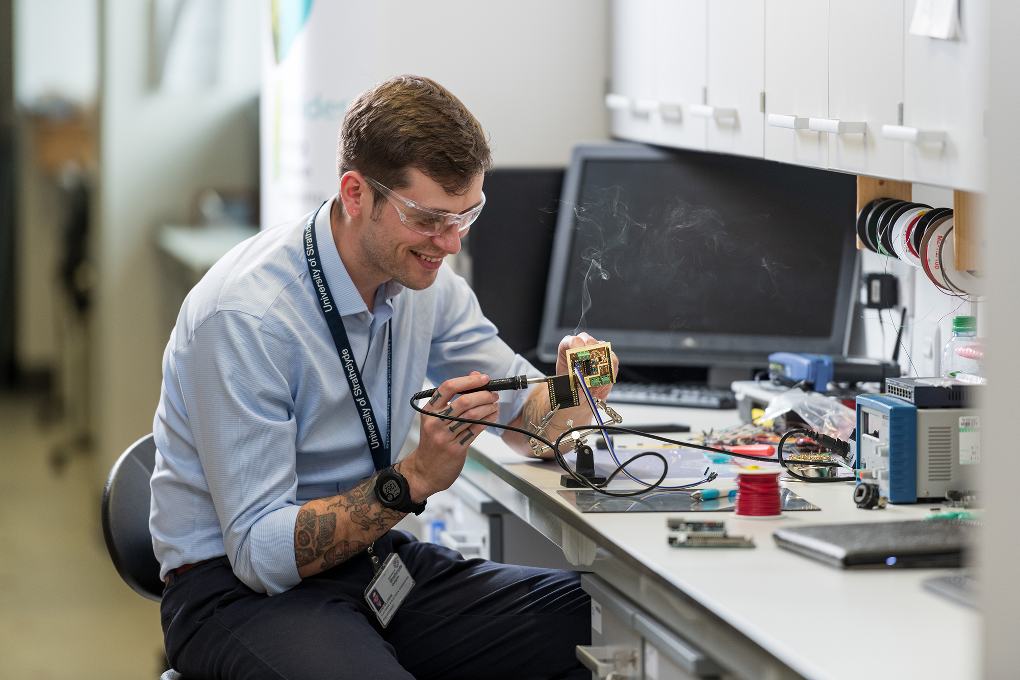 Young male engineer soldering electronic equipment