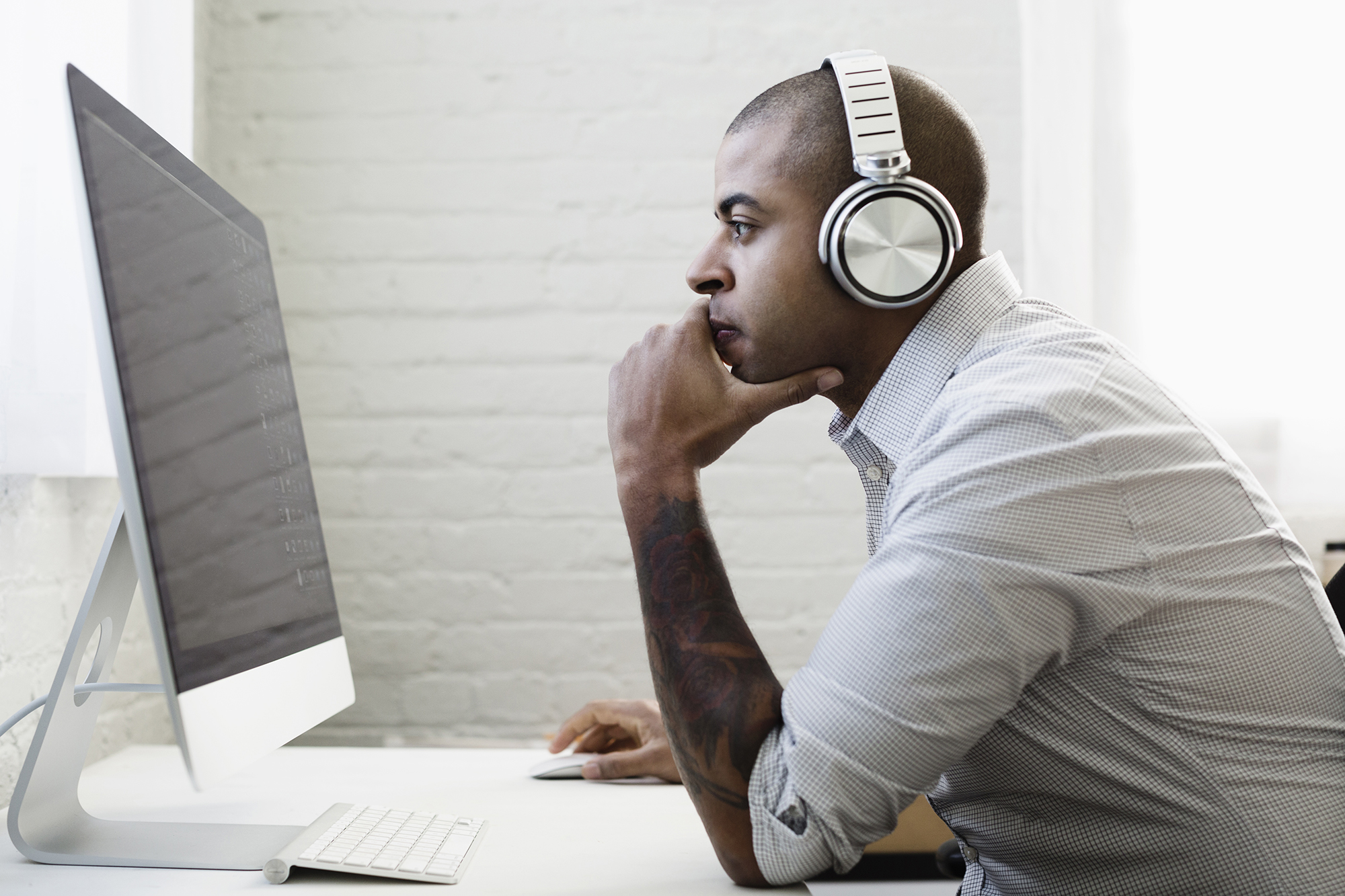 Mixed race businessman listening to headphones and working at desk (1)